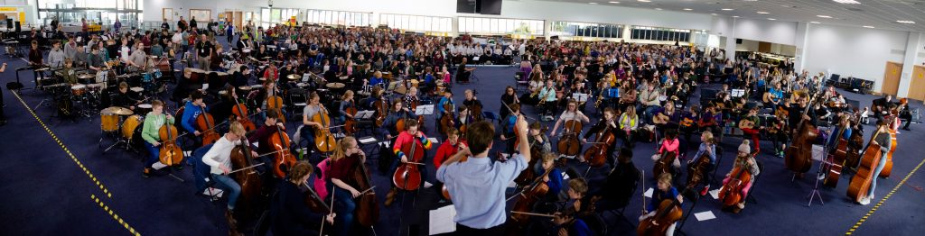 Frank Zielhorst conducts a massed ensemble of school children at a Ferry Terminal in Southampton