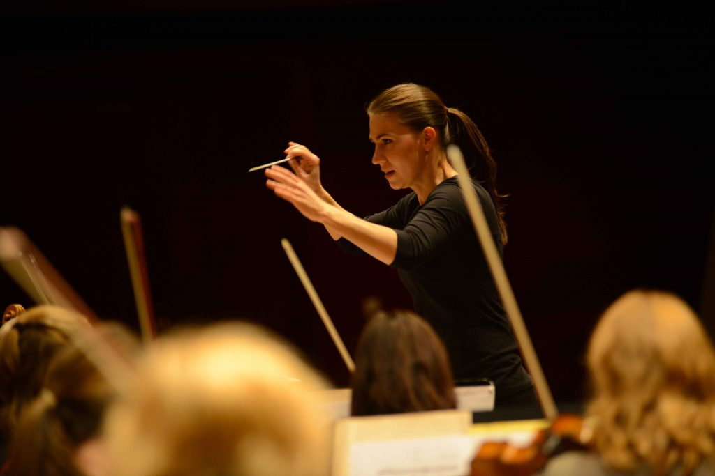 Marta Gardolińska conducts the orchestra with an intense expression