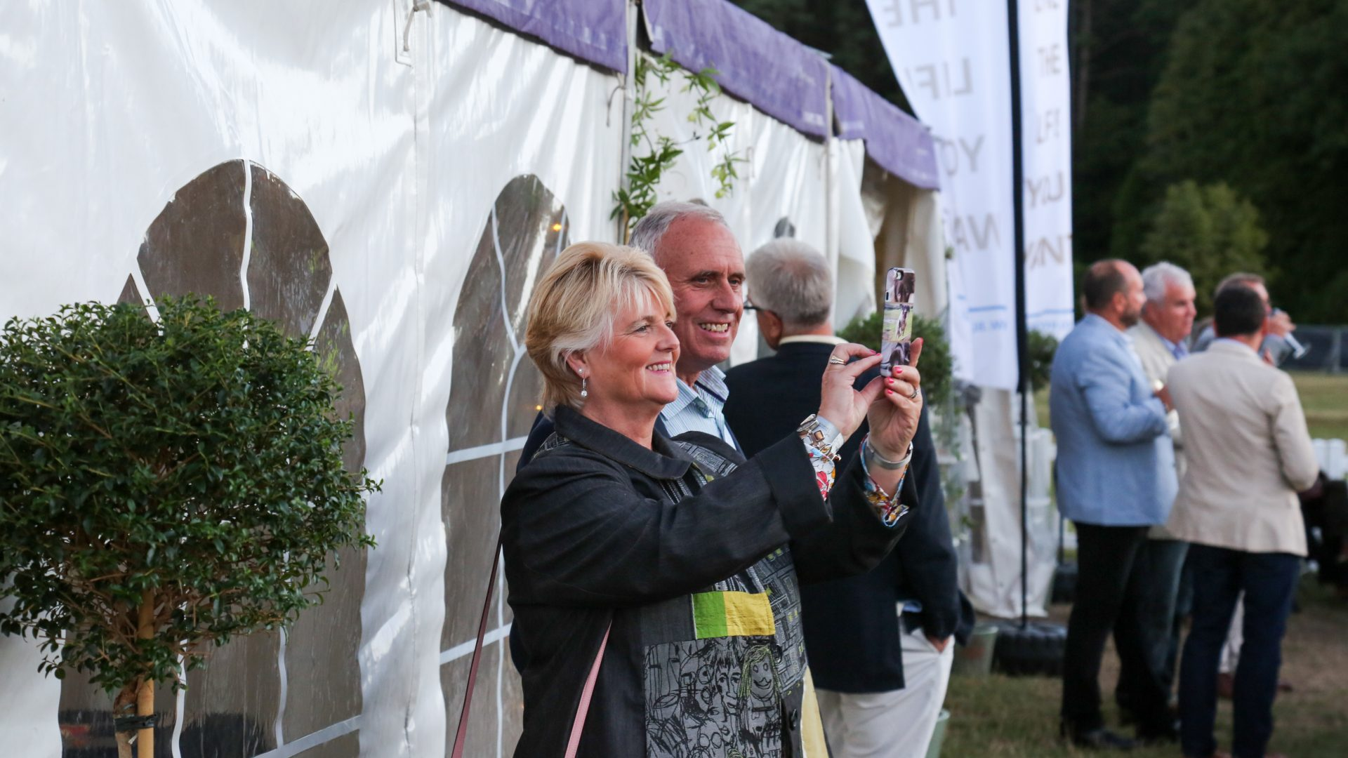 Two guests take a photo in front of the Corporate Guests marquee at the BSO Proms in the Park, which aims to enterain and impress other guests.