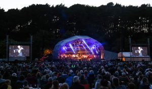 Victor Aviat is seen on two big screens either side of the domed stage at Meyrick Park, conducting our Classical Extravaganza concert