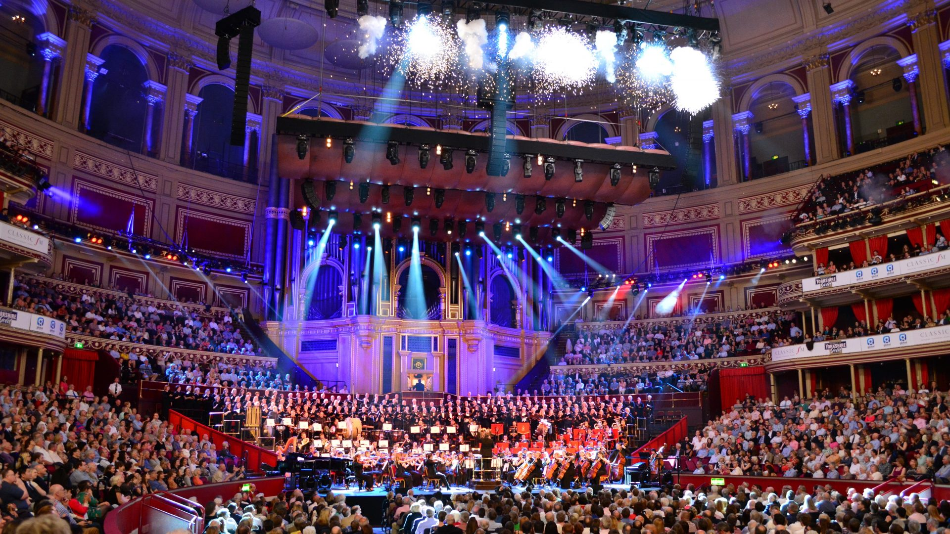 The Orchestra perform on the Royal Albert Hall stage with indoor fireworks and purple lights.